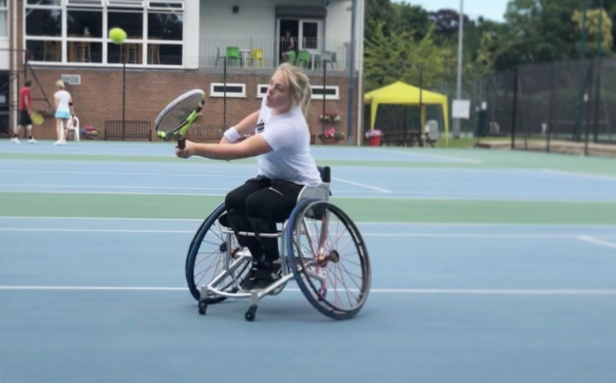 Ruby is on a blue outdoor tennis court. She is playing wheelchair tennis, hitting the ball with her racket.