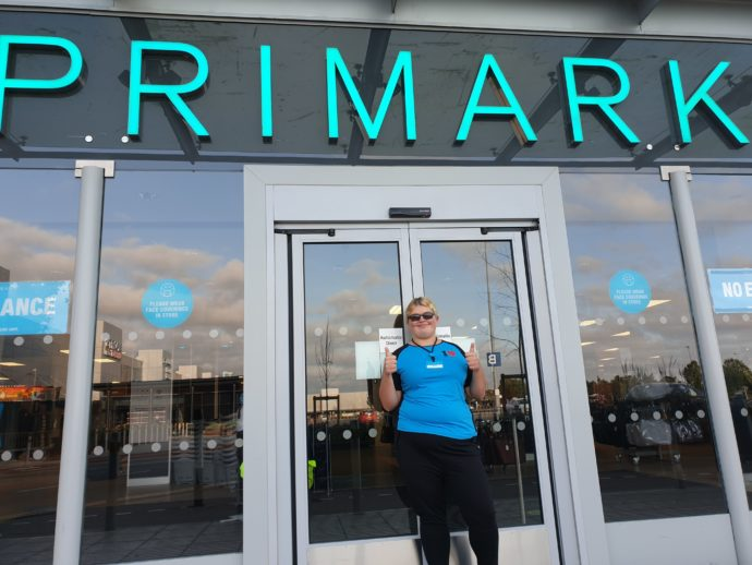 A person stood outside a Primark shop in a Primark uniform.